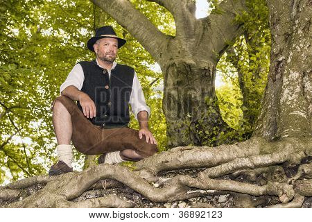 Kneeling Man In Traditional Bavarian Costumes In Forest