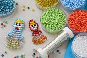 stock photo of beads  - Beaded matreshkas and colorful beads close up - JPG