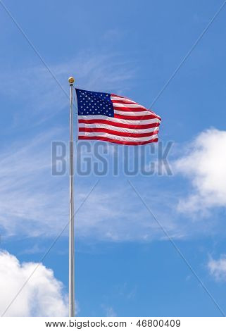 American Flag On Flagpole Waving In Blue Sky