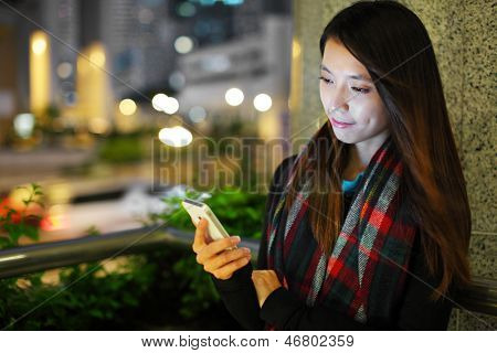 Woman using smartphone in city at night