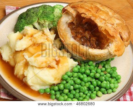Steak & kidney pie with mashed potato, vegetables and gravy.