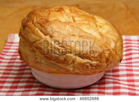 Freshly baked steak pie resting on tea towel. Shallow DoF, focus at centre of image.