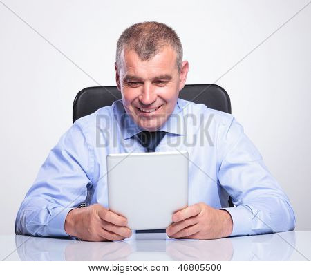 senior bussines man holding and looking at his tablet while at the office with a smile on his face . on gray background
