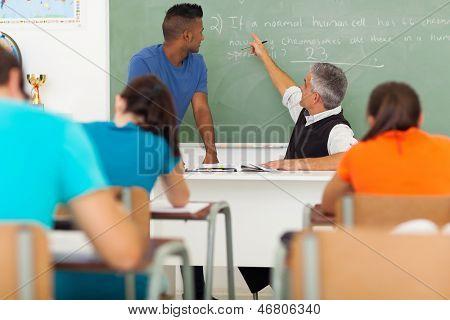 senior high school biology teacher teaching students in classroom
