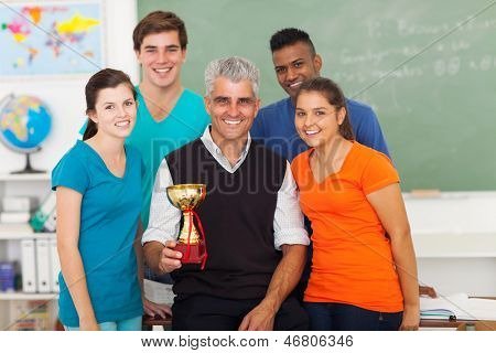 senior teacher and group of high school students holding trophy in classroom