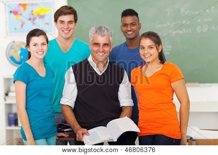 group of cheerful high school students in classroom with senior teacher