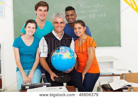 smiling male teacher holding a globe and with teen students