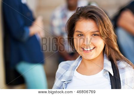 smiling young middle school girl with friends on background
