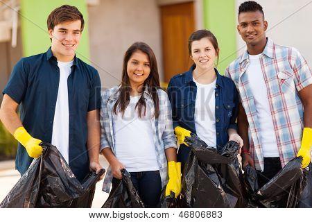cheerful young teenage volunteers with garbage bag