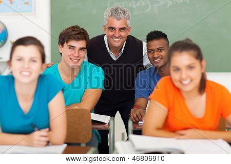 happy middle aged high school teacher with group students in classroom