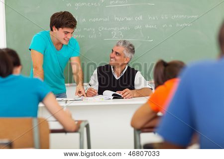 friendly senior high school teacher helping a student with the class work