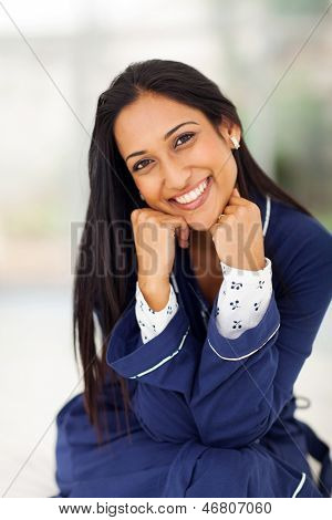 happy indian woman in pajamas sitting in bedroom