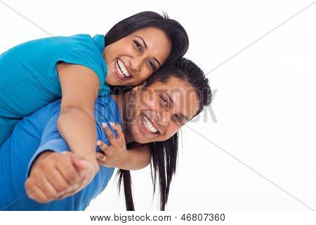 happy young indian couple having fun with piggyback on white background