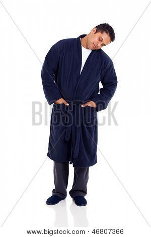 sleepy indian man standing on white background wearing nightgown