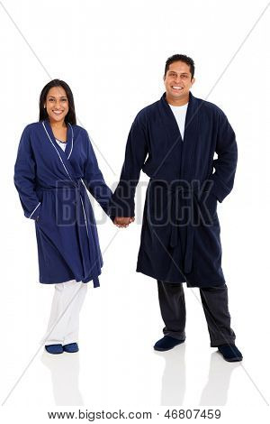 cheerful indian couple in pajamas holding hands standing on white background