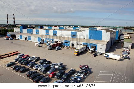 Trucks are loaded and unloaded at a large warehouse, top view of the warehouse and parking.