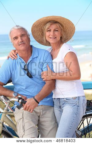 Middle-aged couple enjoying bike ride by the sea