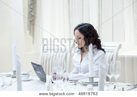 Lovely woman working at computer in restaurant