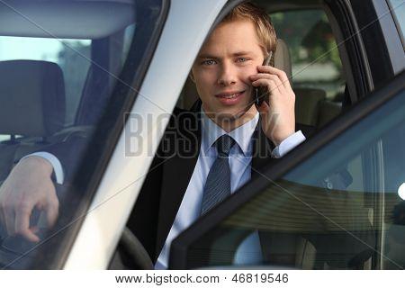 junior executive driving luxury car