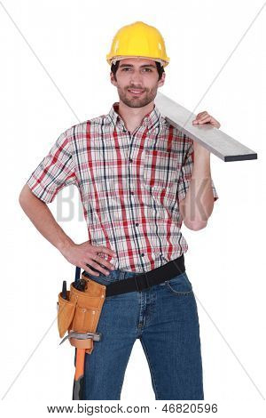 Craftsman with wood plank over his shoulder