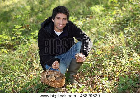 Young man picking wild mushrooms