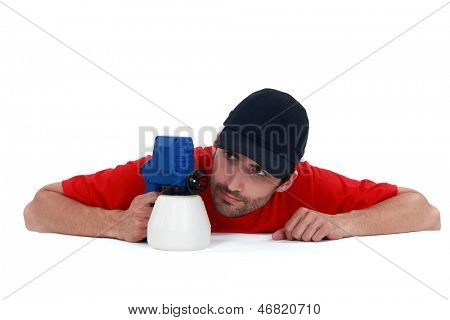 A painter examining his spray gun.