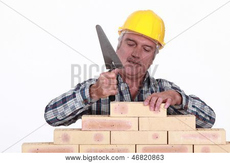 Mason tapping brick into place