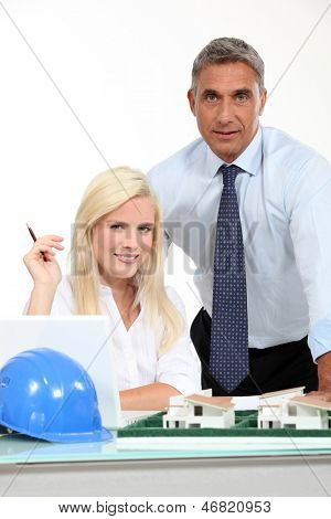 an architect and his assistant behind a district model