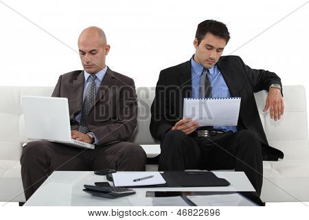Two determined businessmen sat waiting for presentation