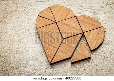 heart version of tangram, a traditional Chinese Puzzle Game made of different wood parts to build abstract figures from them, on white painted barn wood