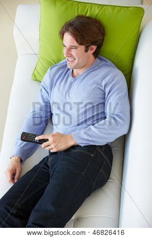 Overhead View Of Man Relaxing On Sofa Watching Television
