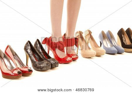 Womans Legs In Shoes In Row Of Shoes