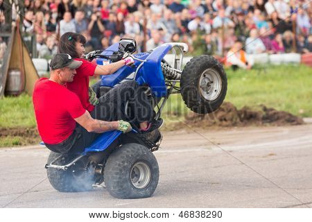 MOSCOW - AUG 25: Man with girl rides on the rear wheels on a quad bike on Festival of art and film stunt Prometheus in Tushino on August 25, 2012 in Moscow, Russia. The festival was organized in 1998.