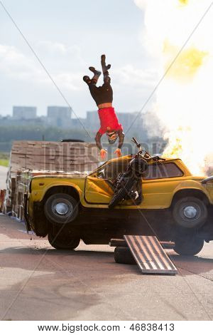MOSCOW - AUG 25: Stuntman flies over the burning car on Festival of art and film stunt Prometheus in Tushino on August 25, 2012 in Moscow, Russia. The festival was organized in 1998.