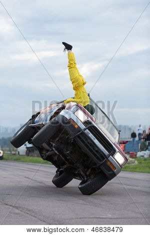 MOSCOW - AUG 25: Stuntman stands upside down on car traveling on two wheels on Festival of art and film stunt Prometheus in Tushino, Aug 25, 2012 in Moscow, Russia. The festival was organized in 1998.