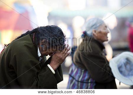 LHASA, TIBET-OCTOBER 07: A Tibetan buddhist pilgrim is praying in front of Jokhang Temple on October 07, 2011 in Lhasa, Tibet.