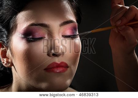 Sexy brunette putting mascara makeup in darkness