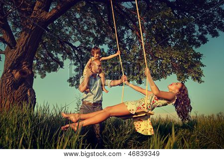 Beautiful mom on the swing in the forest with her family