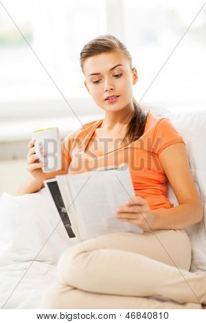 smiling woman with cup of coffee reading magazine at home