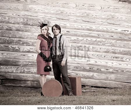 young couple in vintage clothing with luggage