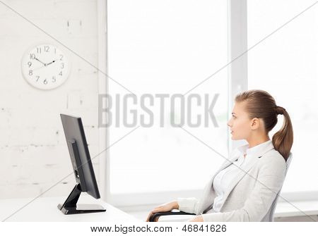 picture of businesswoman looking at wall clock in office