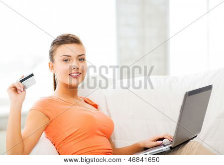 smiling woman with laptop showing credit card at home