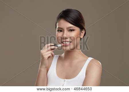Female Asian Applying Lipstick