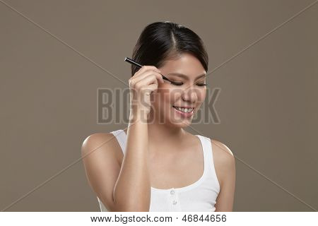 Female Asian Applying Eye Liner