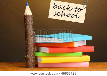 Colorful wooden pencils with books on wooden table on brown background