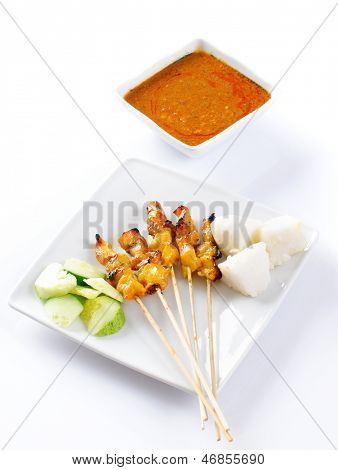 Chicken satay or sate, skewered and grilled meat, served with peanut sauce, cucumber and ketupat. Traditional Malay food. Delicious hot and spicy Malaysian dish, Asian cuisine.
