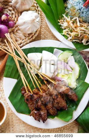 Satay or sate, skewered and grilled meat, served with peanut sauce, cucumber and ketupat. Traditional Malaysian food. Delicious hot and spicy Malay dish, Asian cuisine.