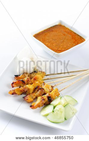 Chicken satay, skewered and grilled meat, served with peanut sauce, cucumber and ketupat. Traditional Malay food. Delicious hot and spicy Malaysian dish, Asian cuisine.