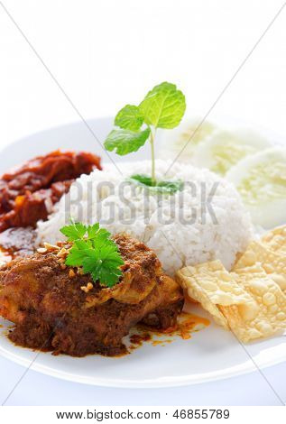 Nasi lemak kukus traditional malaysian spicy rice dish. Served with belacan, ikan bilis, acar, peanuts and cucumber. White background.