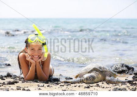 Hawaii girl swimming snorkeling with sea turtles. Happy woman on vacation with snorkel mask lying on Hawaiian sand on Big Island next to sea turtle. Hawaii, USA travel lifestyle image.